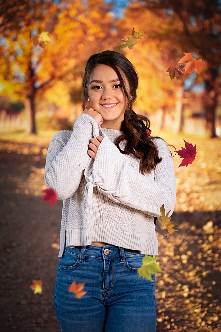 High school senior girl in off-white sweater standing along a tree-lined path with fall leaves swirling around her at Round Hill Park in Elizabeth, PA