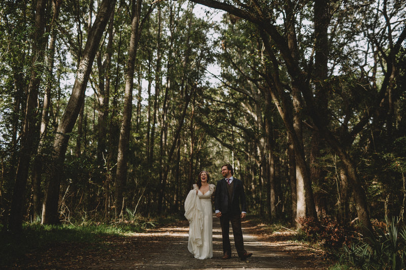 wedding couple laughing on a dirt road