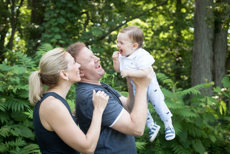 Dad holding toddler in the air with mom smiling at them