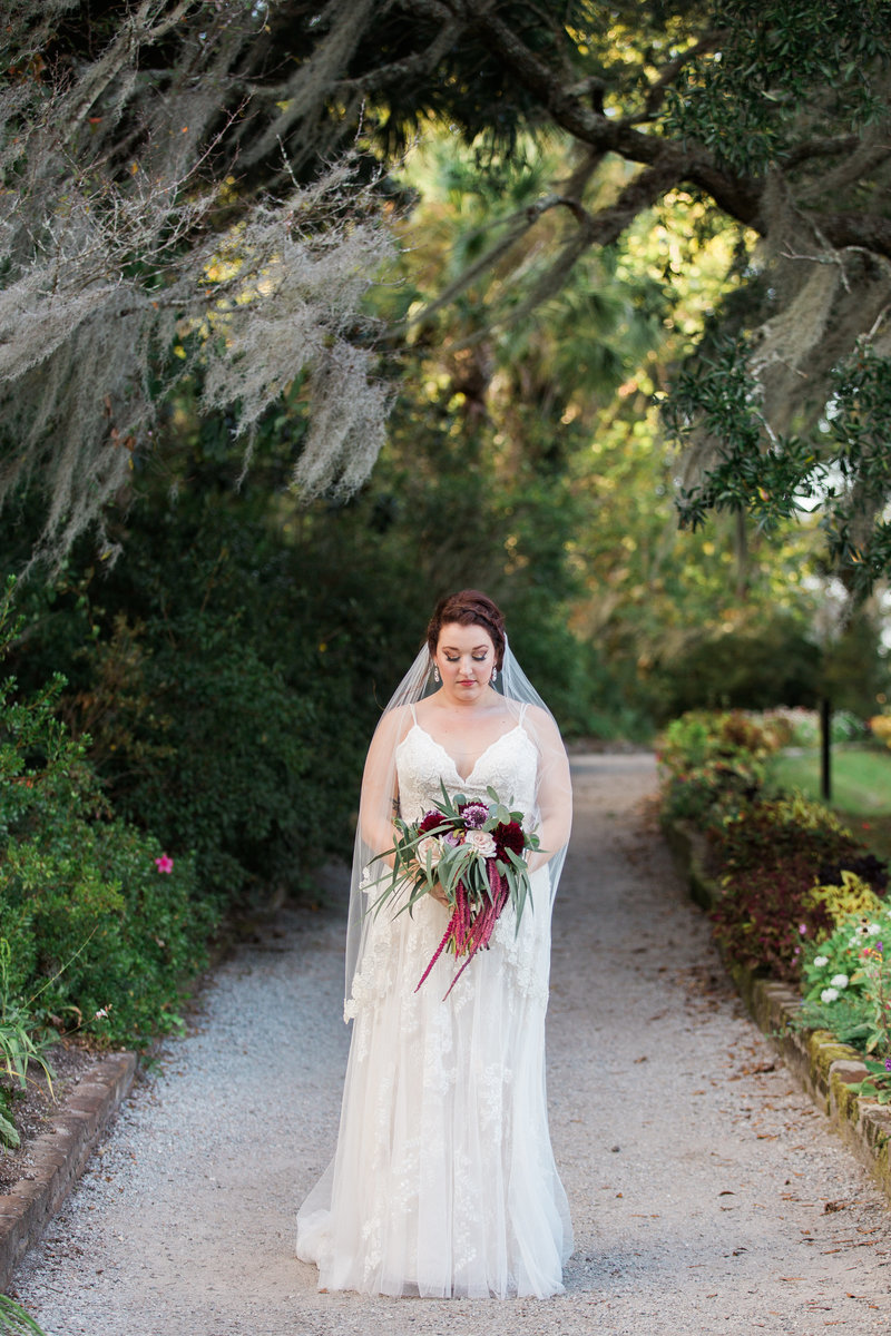 Bride standing alone on a path holding bouquet
