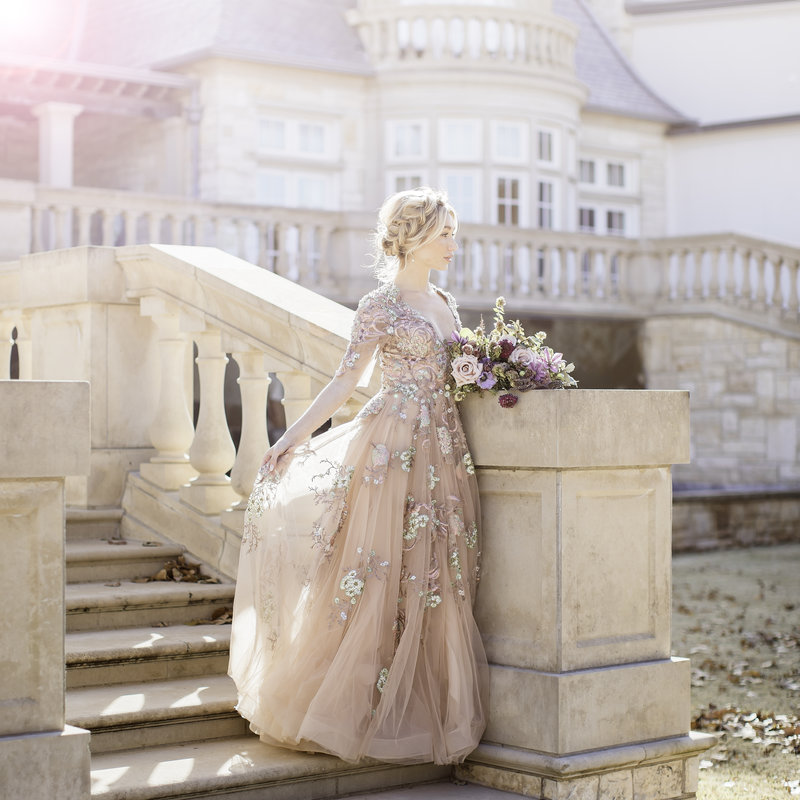 Blond bride standing on staircase with flower bouquet