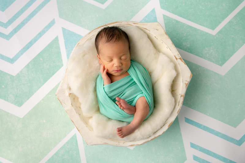 newborn boy swaddled in teal on a chevron background