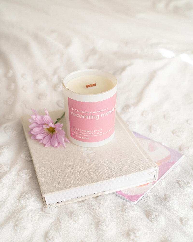 Soy wax candle and flower on a journal in a white bed.