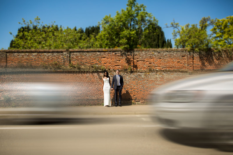 A couple pose naturally for a portrait on their wedding day witht ehir backs to a large brick wall and cars racing by in the foreground at long melford suffolk.