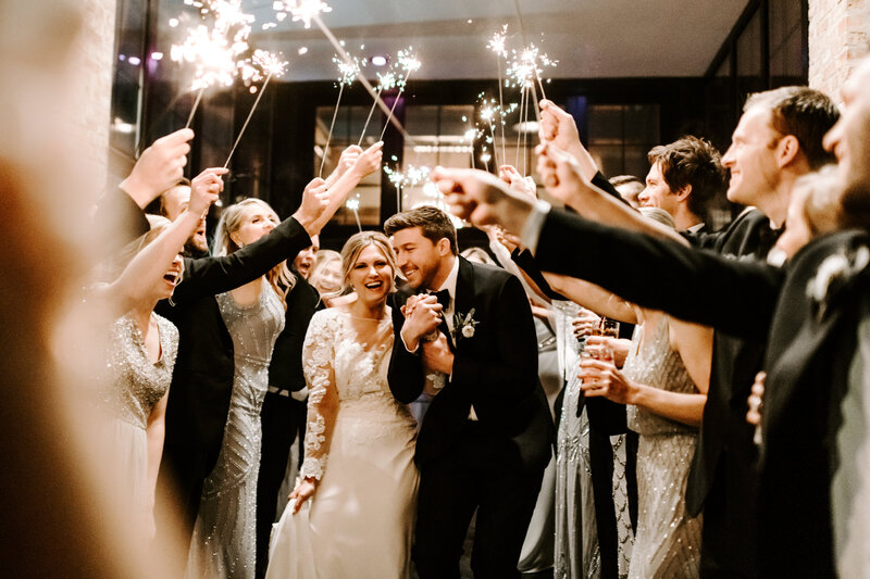 bride and groom surrounded by wedding guests holing sparklers