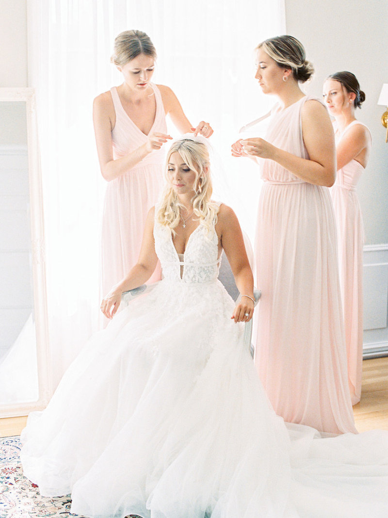 Bride getting ready with her bridesmaids. Bridesmaids are dressed in pink dresses