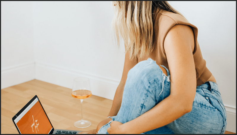 Woman working on laptop next to a glass of wine