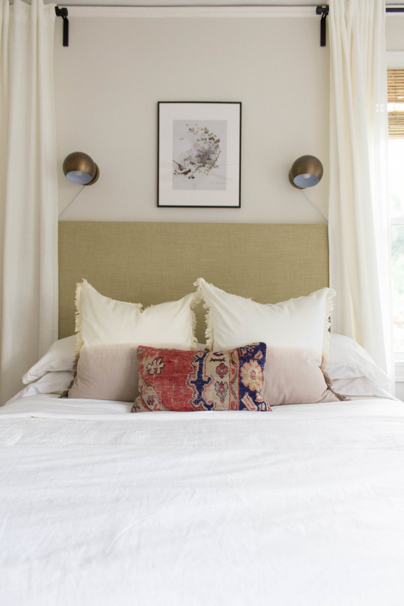 Brass eyeball sconces above bed with rug pillow