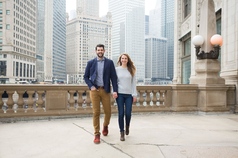 couple walking holding hands in front of chicago wrigley building