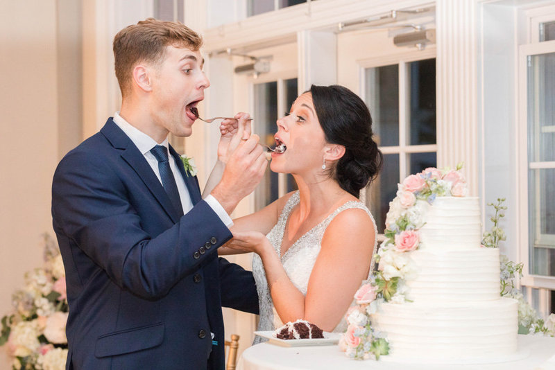 bride and groom eating cake at springfield manor winery and distillery wedding by costola photography