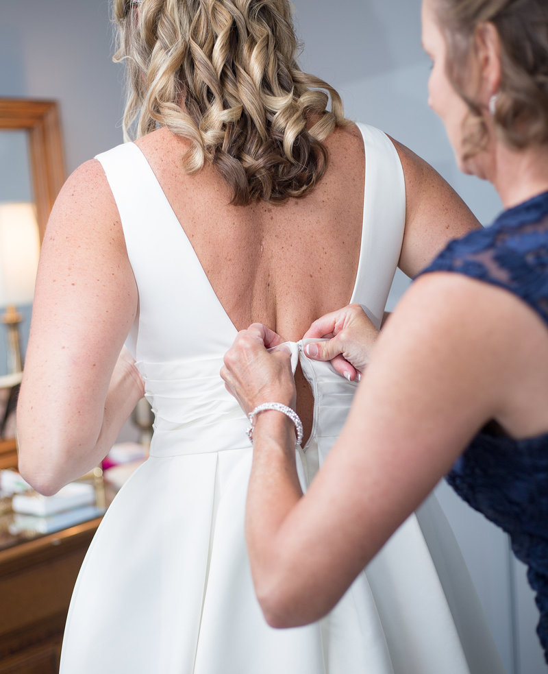 Mother helps her daughter into her wedding dress
