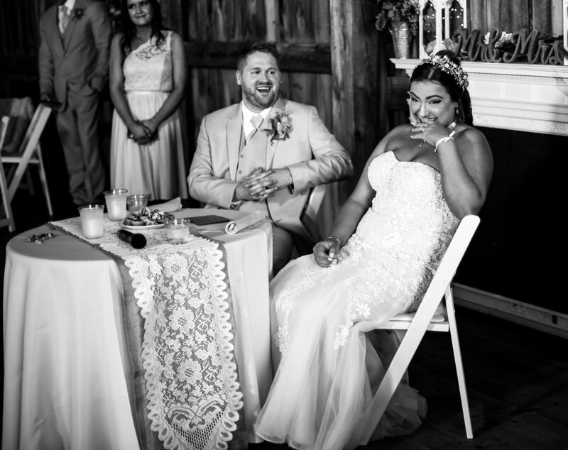 Bride and groom laughing during the toasts at Port Farms wedding reception