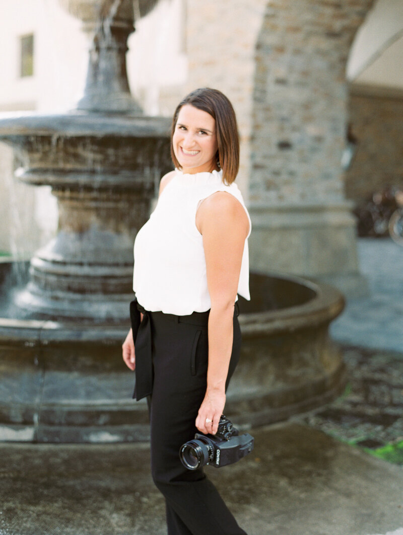 Courtney Bowlden smiling at camera in front of fountain holding camera at her side