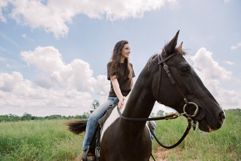 Happy girl on horseback in an open Georgia pasture