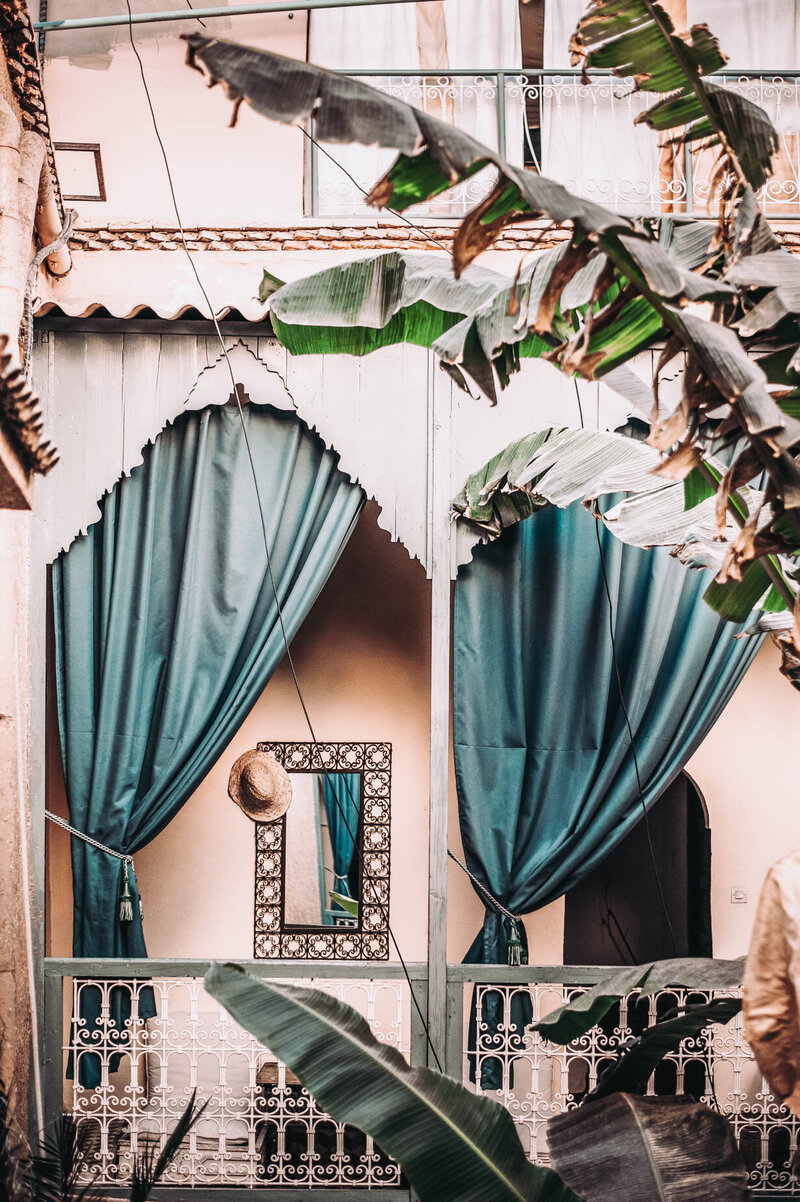 Luxury Hideaway Vacation with Peach Hotel, Terracotta shingles, and teal outdoor curtains