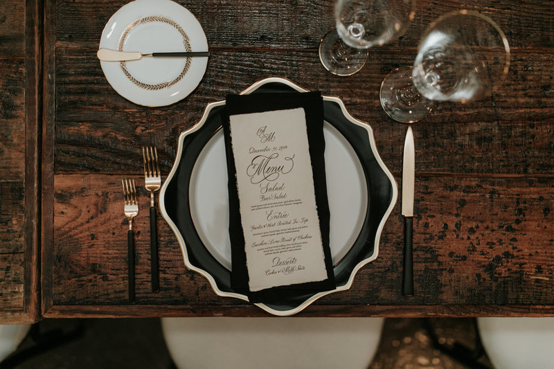 Wedding reception table setting with black rimmed plates and black cutlery