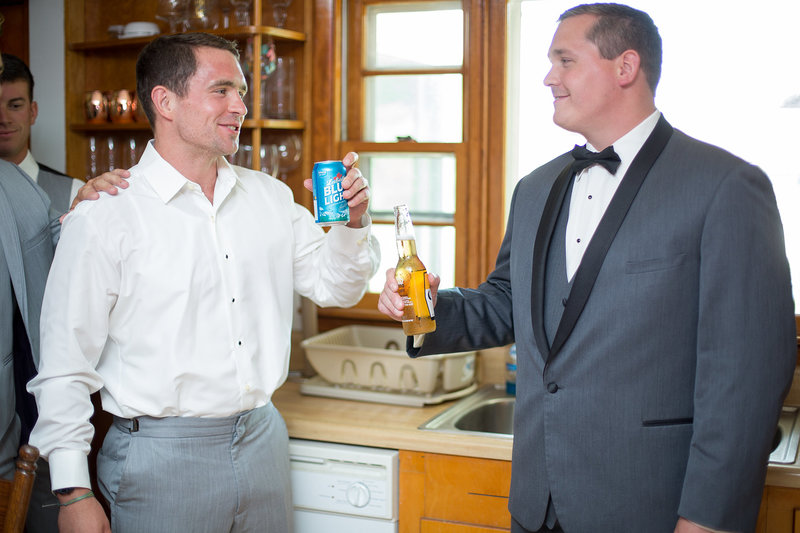 Groom and his brother share a beer while getting ready for wedding