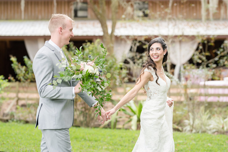 Bride looks back as she leads her groom holding her bouquet outdoors