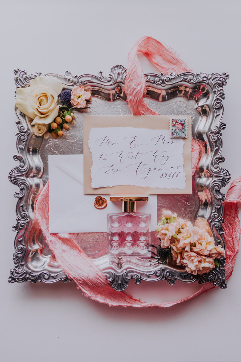 Reno wedding photographers an ornate pink wedding invite adorned with florals