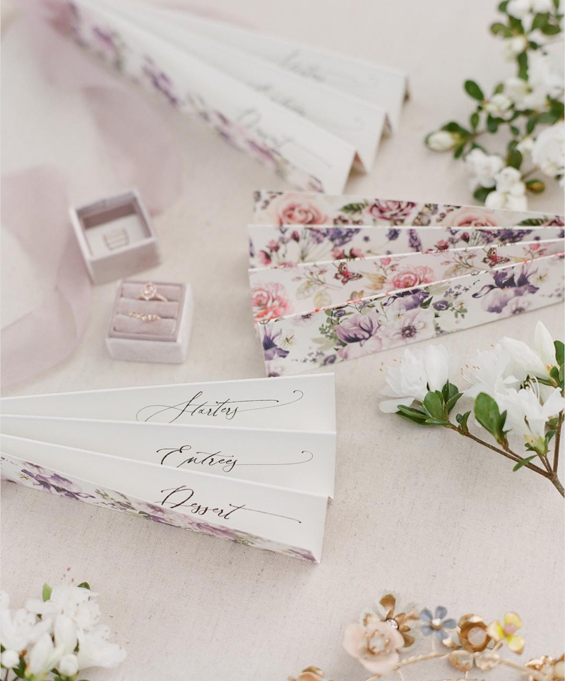 Custom fan wedding menus featuring a pastel botanical print and whimsical calligraphy