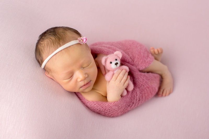 Newborn girl swaddled in pink holding a pink teddy bear