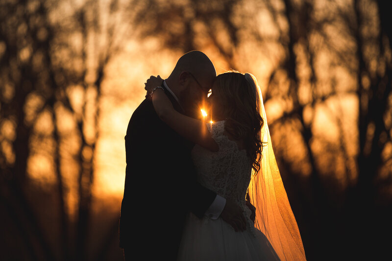 The sun is lighting a bride's vail in a wedding portrait captured during the golden hour.
