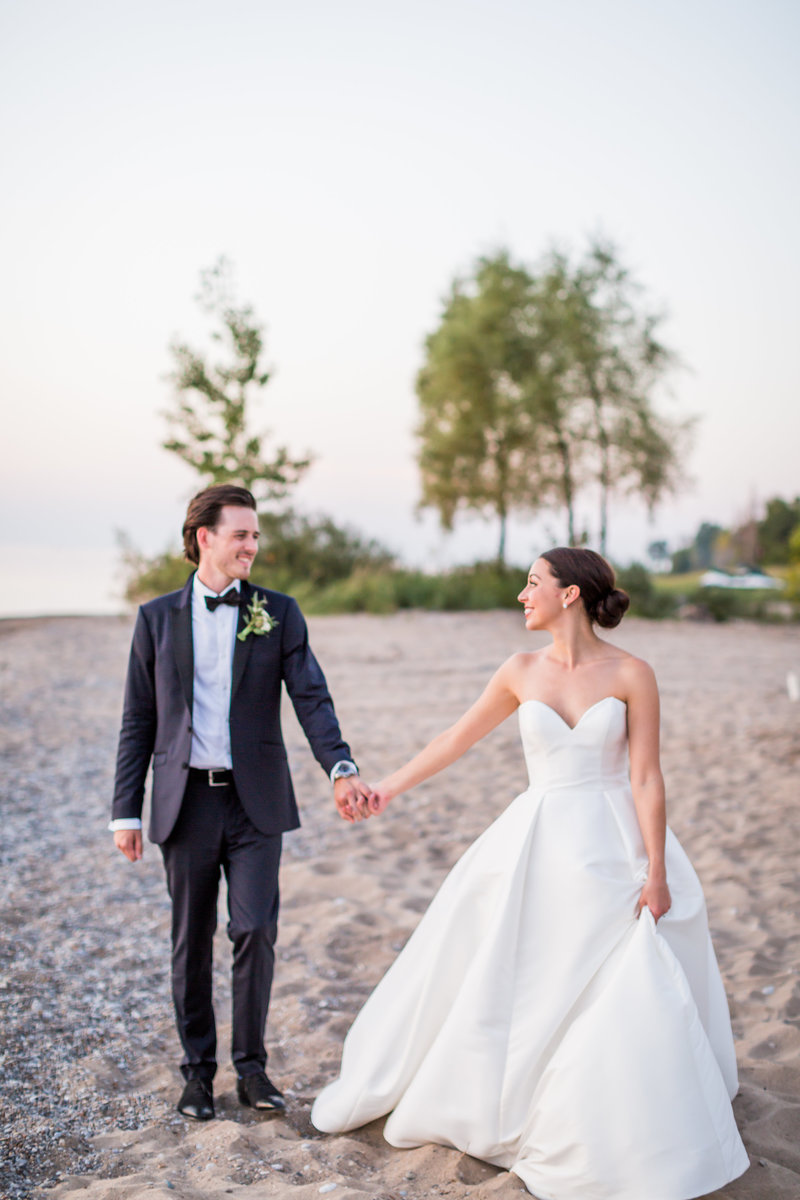 Bride and groom holding hands walking along the beach during sunset
