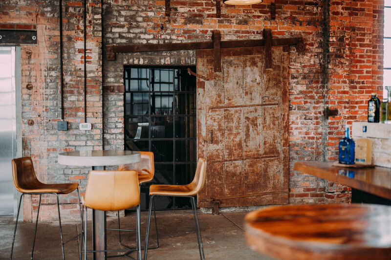 a table sits in front of a brick wall with sliding metal door and window in philadelphia distilling company shot by philadelphia wedding photographer alex medvick