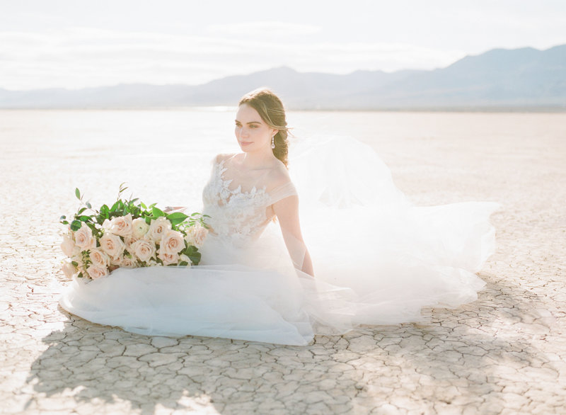 Windswept bride sits in desert holding bouquet