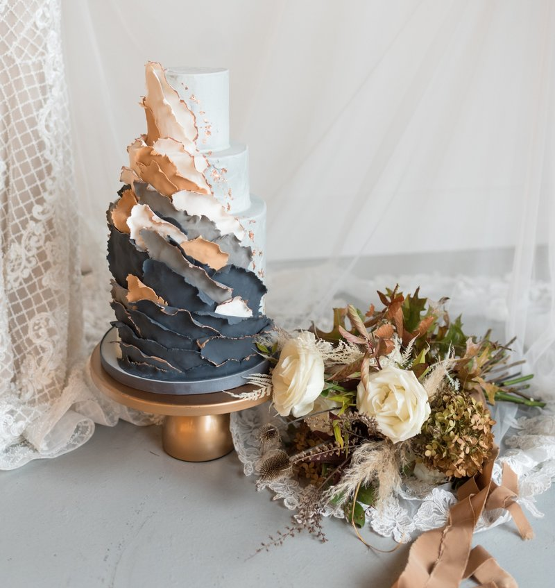 navy ruffled wedding cake next to dried floral bouquet
