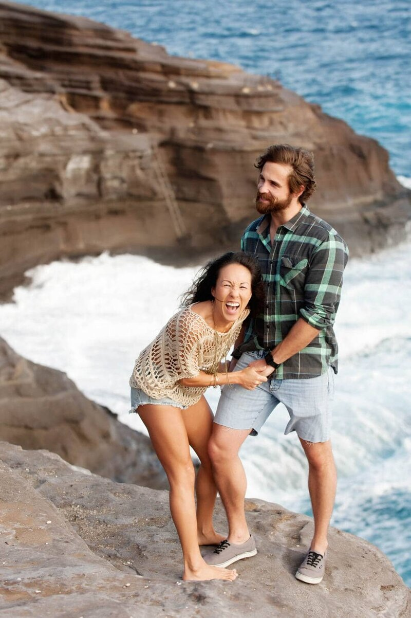 a woman laughs while holding a man's hands at spitting caves in hawaii