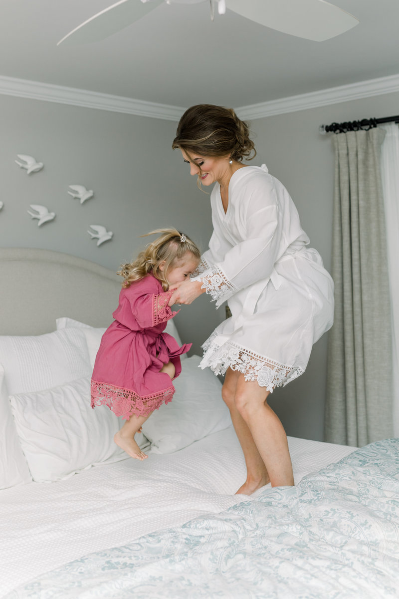 Virginia Wedding Photographer, bride jumping in bed with flower girl