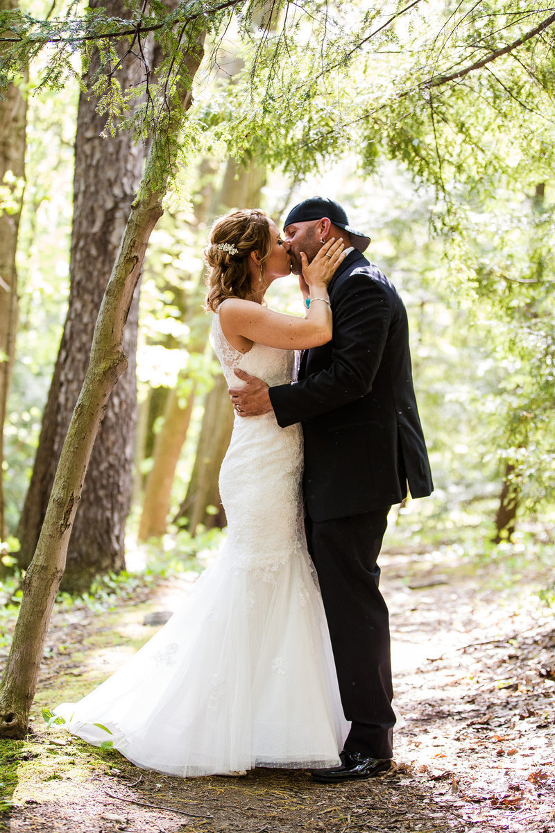 Bride and groom kiss in clearing of trees on the Penn State Behrend campus in Erie, PA