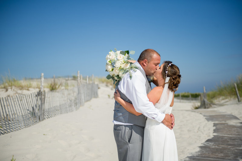 bride and groom kiss on beach walkway