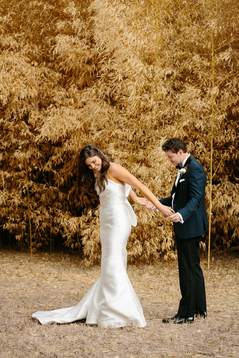 bride in strapless wedding dress smiling at groom in blue suit wiping away tears surrounded  by trees with orange leaves