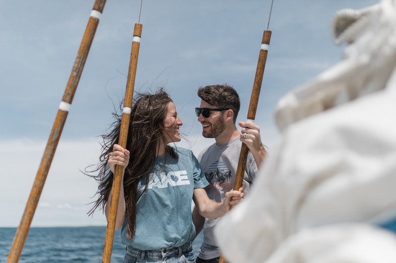 mand and woman standing on sail boat smiling at each other