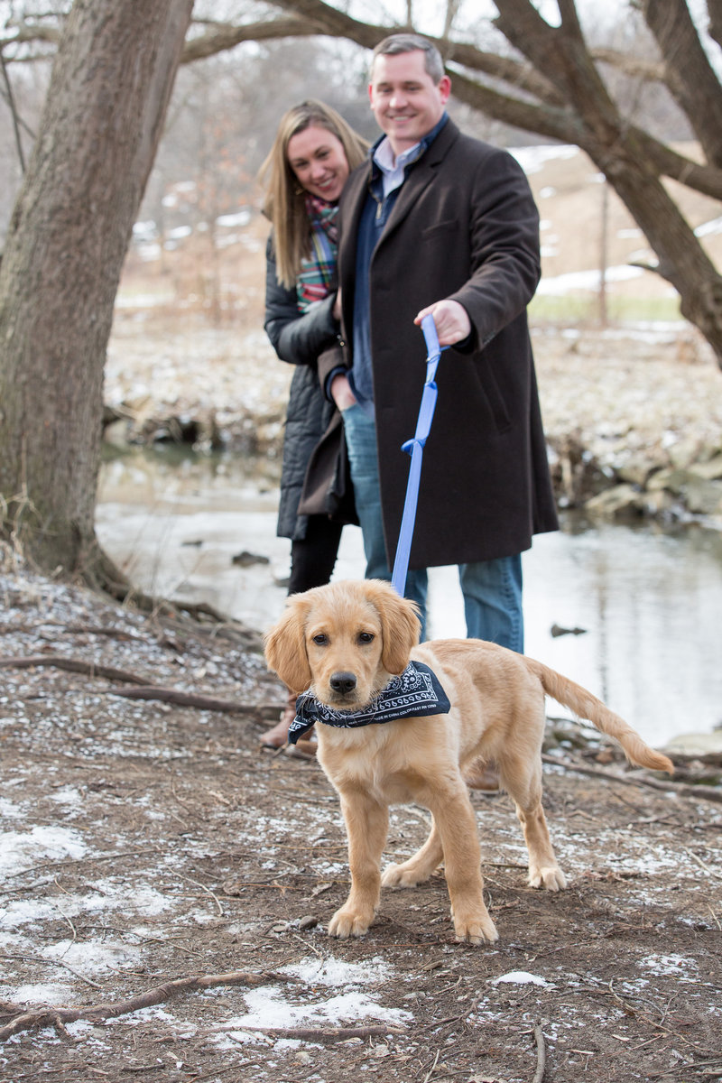 Engaged couple walk their dog through Frontier Park during winter engagement photo session