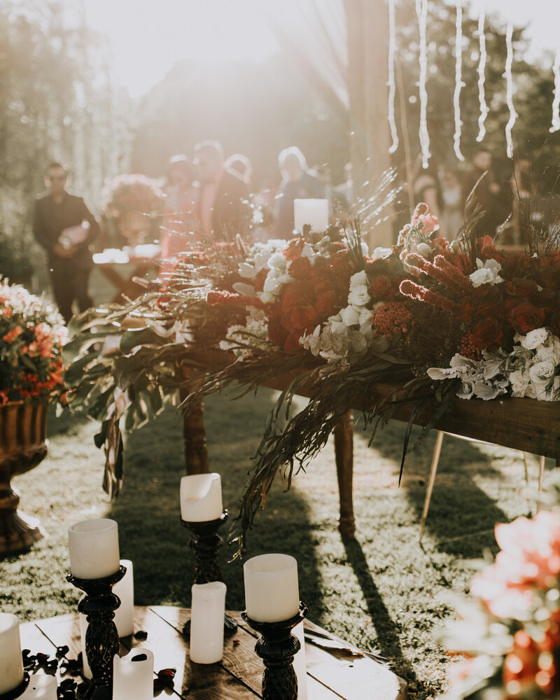 Deep red flowers lie on a wooden table outdoors at a wedding party reception surrounded by pillar candles.