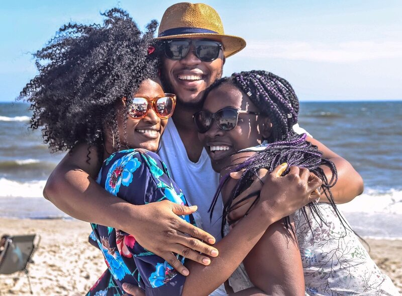 two-women-with-man-hugging-by-the-sea-936018