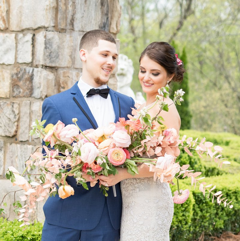 Columbus Ohio  couple on their wedding day admire a large bouquet