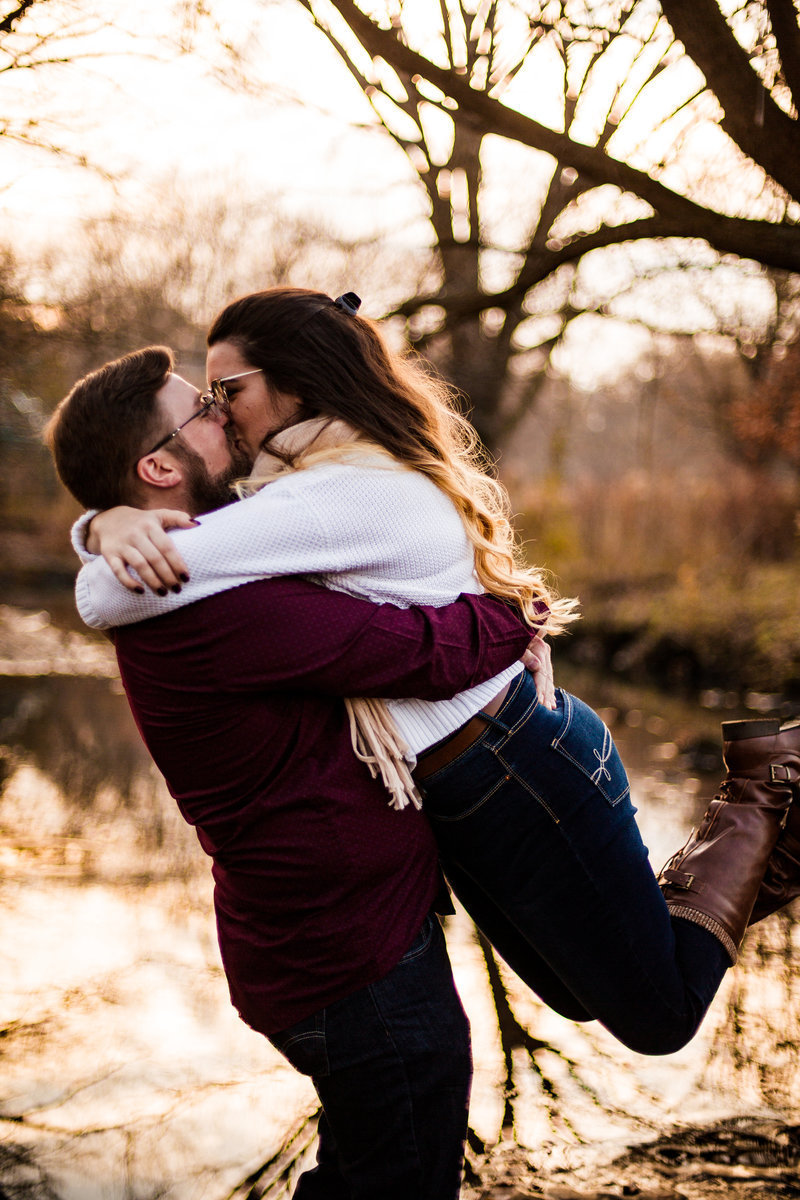 Man hugs and lifts his fiancee during fall engagement photo session