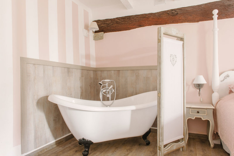 Roll-top bath in the Garden Suite in Casa Fiore holiday home in Tuscany. Chalk paint 'For the love of Tan' nr 44 on the wall. Interior design by Arte di Vita.