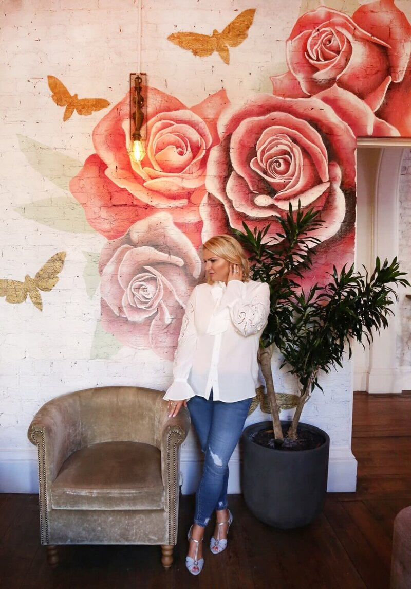 Charlotte standing in front of a rose painted wall
