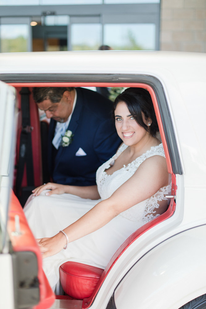 bride getting into white classic luxury car  at Stone House at Stirling Ridge Maryland Wedding by  Costola Photography