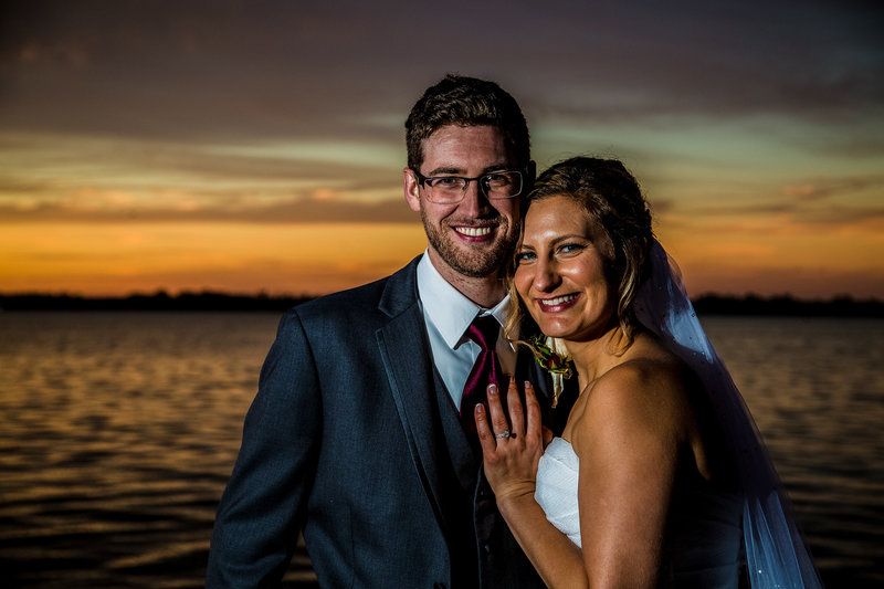 Bride puts hand on groom's chest outside Sheraton Erie Bayfront Hotel at sunset