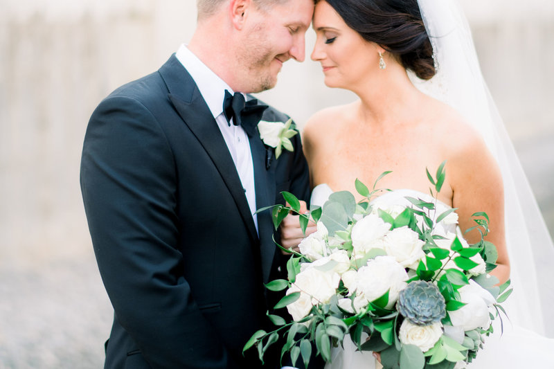 close up bride and groom with heads together and black tie tux