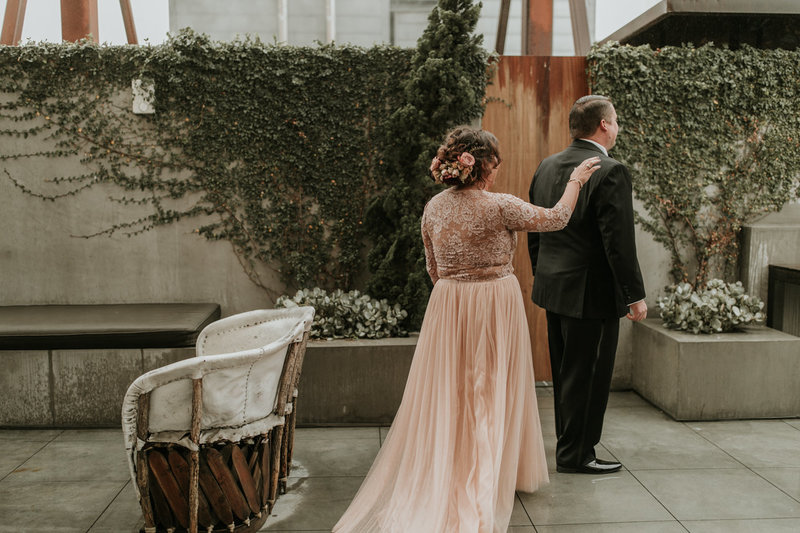 Bride in blush wedding dress during first look with groom at this Natural History Museum wedding on New Years Eve