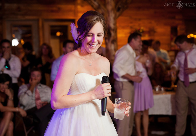 Happy bride at her wedding reception in the rustic barn at Mountain View Ranch in Colorado