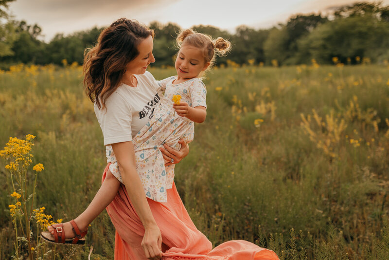 mom spinning with daughter in a field