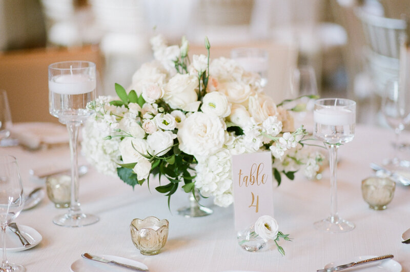 Close up of reception table decorated with white bouquet, small candles, silver cutlery, and tall glasses with candles floating in water